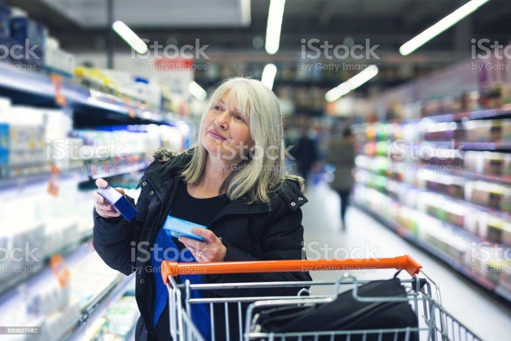 Beautiful lady in a supermarket choosing cosmetics
