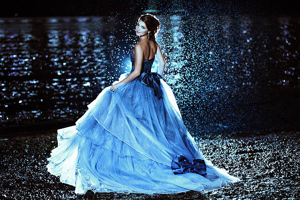 schöne frau im blauen kleid - lange abendkleider stock-fotos und bilder