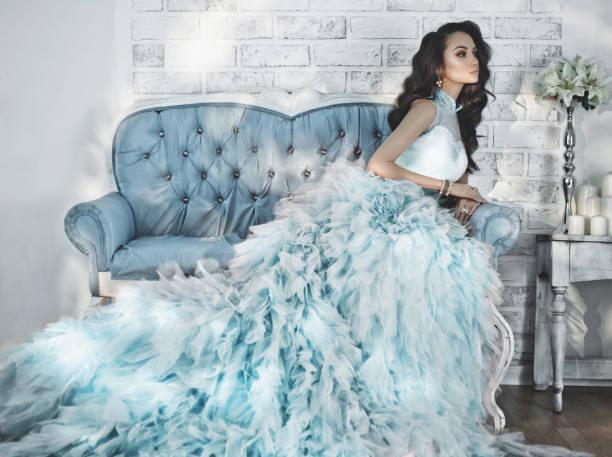 schöne dame im wunderschönen couture kleid auf sofa - soup_studio stock-fotos und bilder