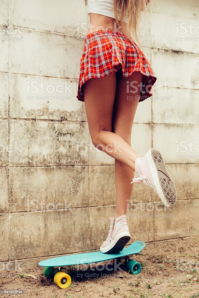 beautiful lady in mini skirt trying get over the fence stock photo