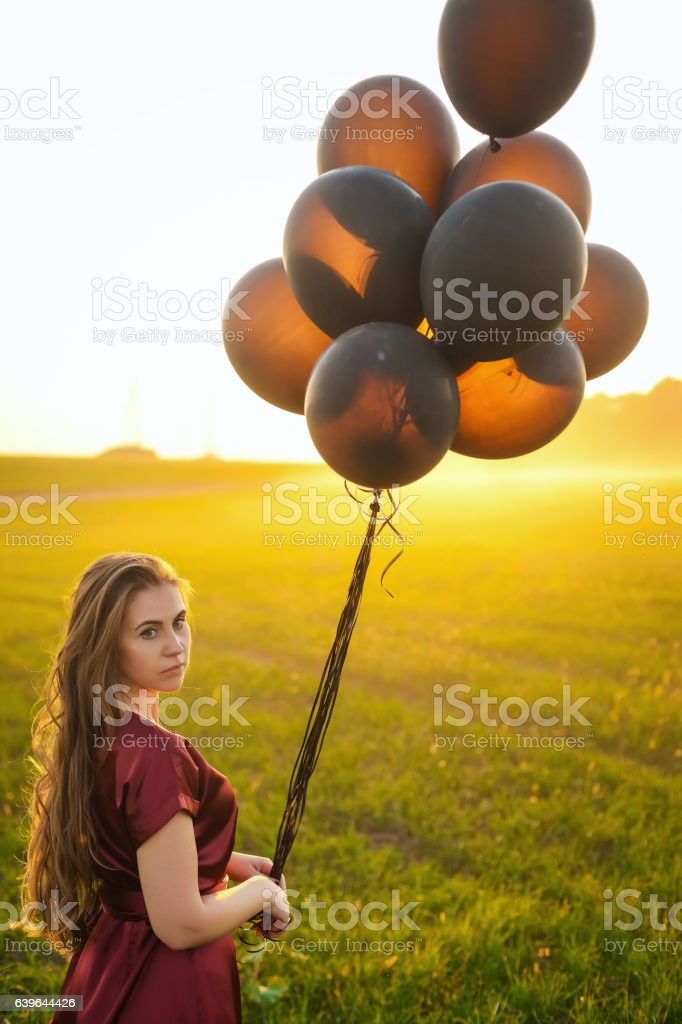 beautiful lady in red dress with black balloons at sunset stock photo