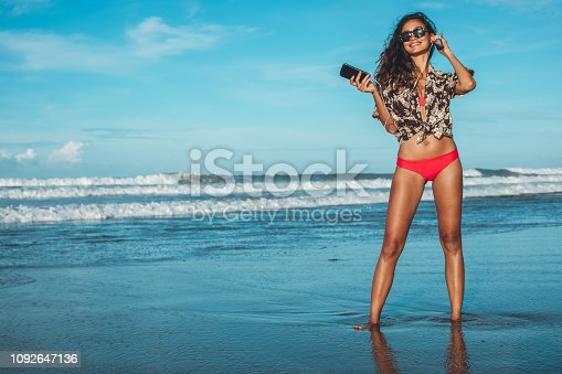 One woman, young and beautiful girl on the beach on sunny day, using smart phone, listening music on headphones.
