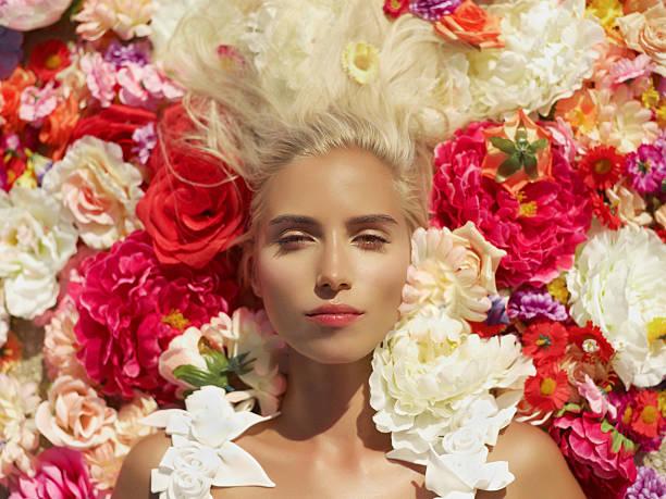 Beautiful lady lying in flowers stock photo