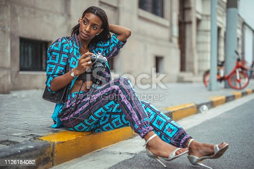One woman, modern black young lady in city, sitting on sidewalk, holding a camera.