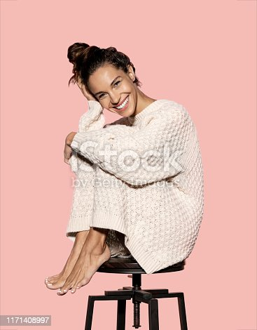 Full length portrait of gorgeous woman with tan skin. Cheerful model wearing snow white knitted dress sitting on chair hugging knees. Beauty and fashion concept. Isolated on pink