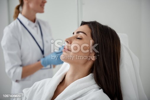 Side view portrait of attractive woman in white bathrobe lying with closed eyes during medical procedure