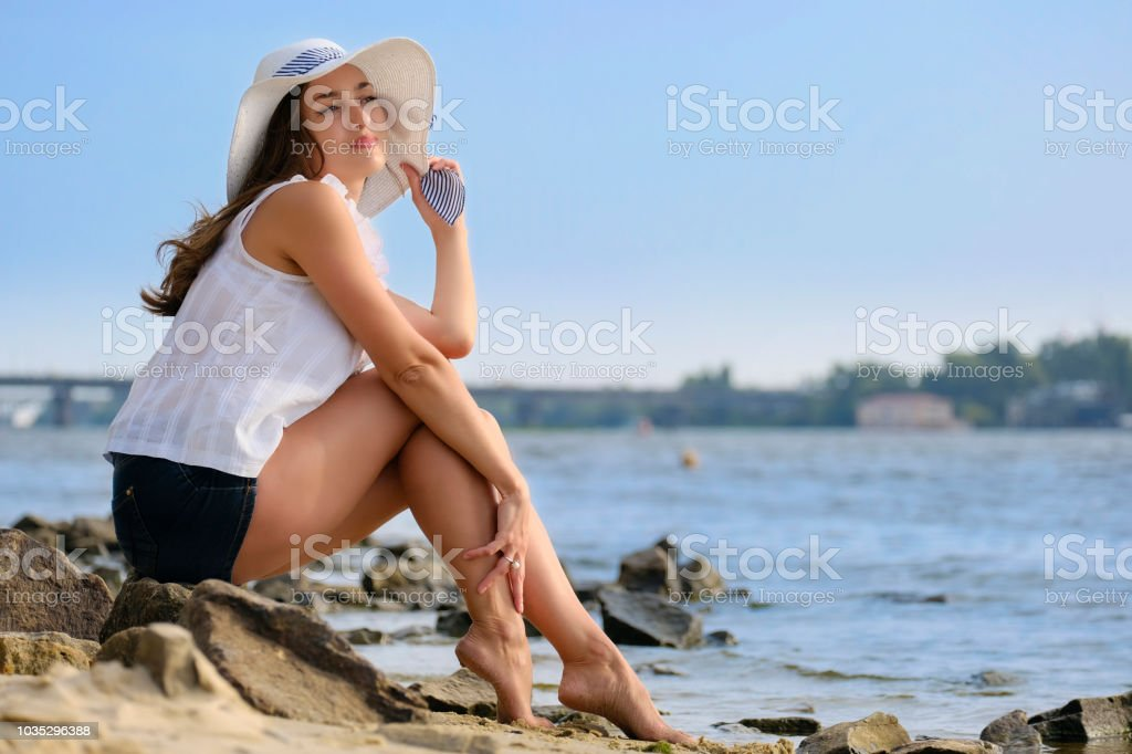 Beautiful lady sits on the shore stock photo