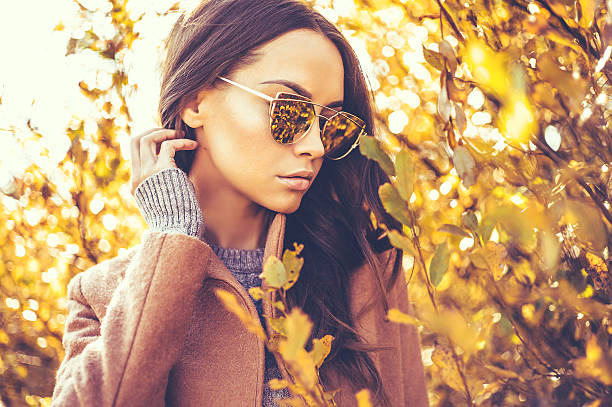 hermosa dama rodeado de hojas otoñales - moda de otoño fotografías e imágenes de stock