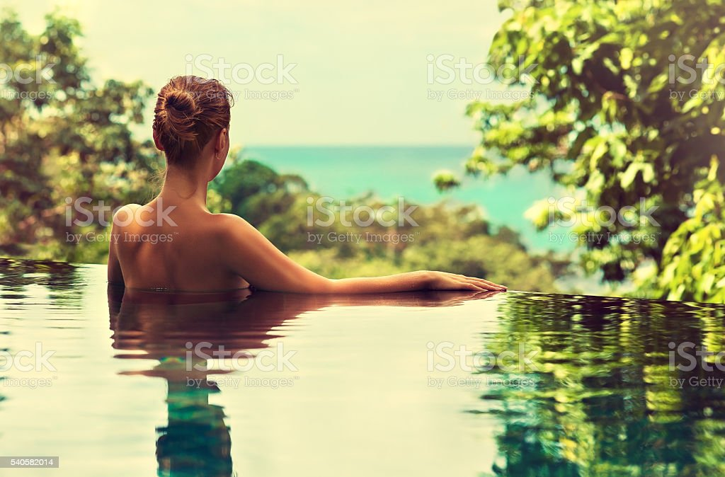 Beautiful lady  watching a sea line from the swimming pool. stock photo
