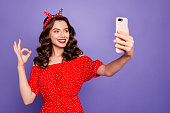 Beautiful lady with telephone in hands making selfies show okey symbol wear off-shoulders dress isolated purple background