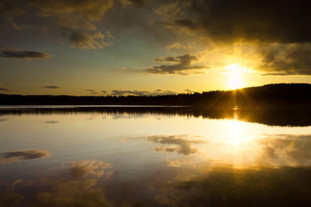Beautiful Lake in Montana with Sun Disappearing Behind Trees stock photo