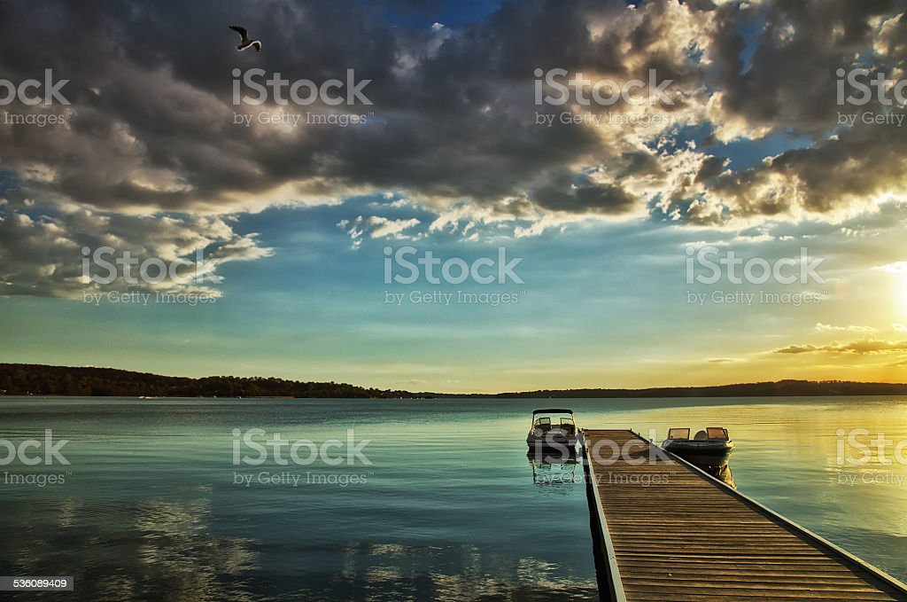 Beautiful Lake Macquarie sunset with jetty and motor boats stock photo