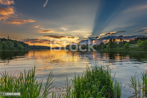 Landscape with beautiful still waters of lake surrounded by grass, forests and colorful golden sunset on summer day. Nature sceneries concept