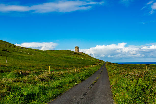 Beautiful landscape of a road between the Irish countryside with the Doonagore Castle tower in the background Beautiful landscape of a road between the Irish countryside with the Doonagore Castle tower in the background in the coastal town of Doolin, Wild Atlantic Way, sunny day in County Clare in Ireland county clare stock pictures, royalty-free photos & images