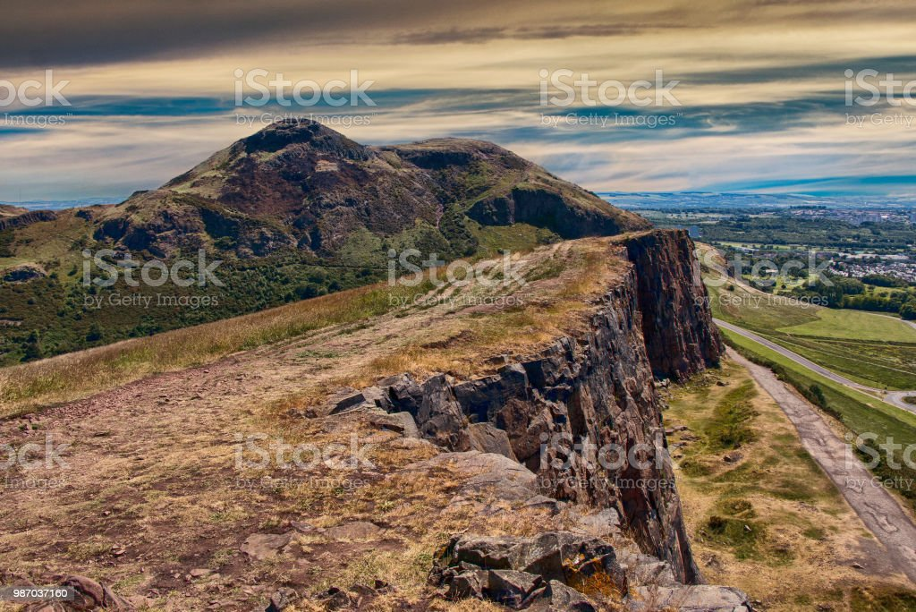 Beautiful landscape of Arthur's Seat mountain in Scotland with path on the cliff and Edinburgh city in the background stock photo