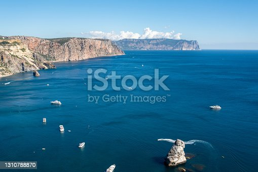 istock Beautiful landscape of Black sea coast  in sunny day with clear sky. Summer seascape with  sailing boats or yachts . Sevastopol, Fiolent Cape, Crimea. 1310788870