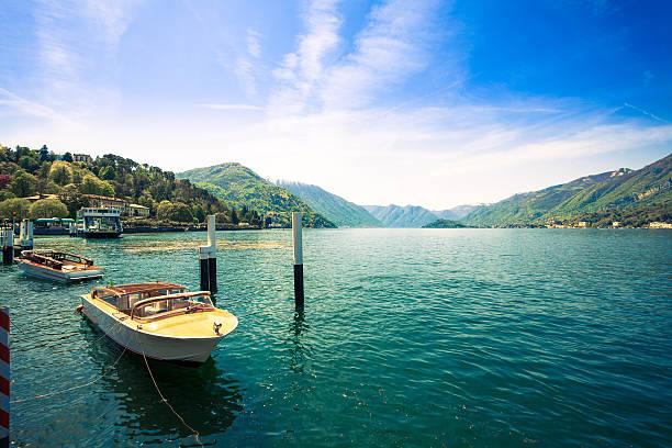 beautiful landscape on como lake and boats, italy - como italië stockfoto's en -beelden