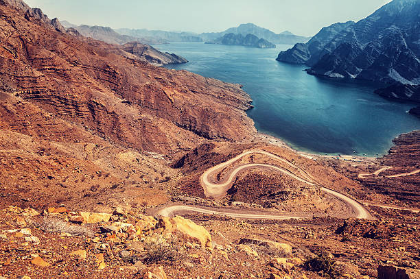 Beautiful landscape Beautiful landscape, curve road in dry arabian mountains over sea, exotic travel to the arab country, travel and tourism concept riverbed stock pictures, royalty-free photos & images
