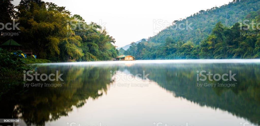 Beautiful landscape river Kwai Yai with mountain in the morning and sun-up and see homes near lake at Kanchanaburi in Thailand, Travel concept. stock photo