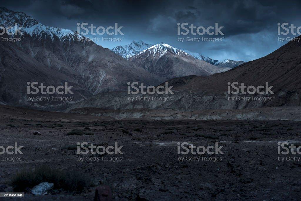 Beautiful landscape snow mountains at night on blue cloud background. Leh, Ladakh, India. stock photo
