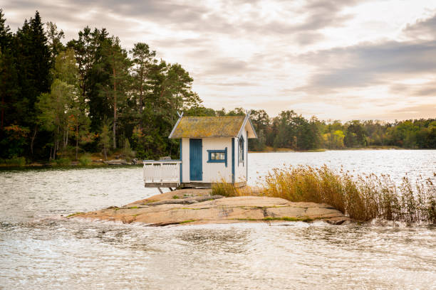 Beautiful landscape view of a small bath hut cottage on a rock in a lake surrounded by trees and reed. stock photo