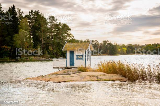 Photo of Beautiful landscape view of a small bath hut cottage on a rock in a lake surrounded by trees and reed.
