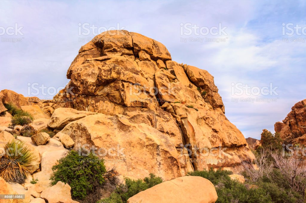 Beautiful landscape view of boulders, red rock formations, grass, cactuses from the hiking trail in Joshua Tree National Park, California, United States. stock photo