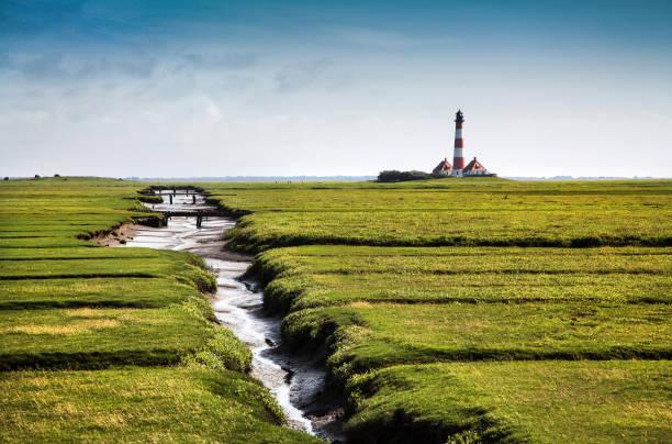 wunderschöne landschaft mit berühmten westerheversand leuchtturm im hintergrund an der nordsee in nordfriesland, schleswig-holstein, deutschland - sylt urlaub stock-fotos und bilder