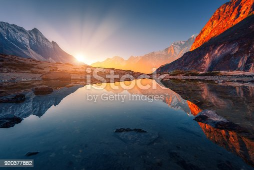 istock Beautiful landscape with high mountains with illuminated peaks, stones in mountain lake, reflection, blue sky and yellow sunlight in sunrise. Nepal. Amazing scene with Himalayan mountains. Himalayas 920377882