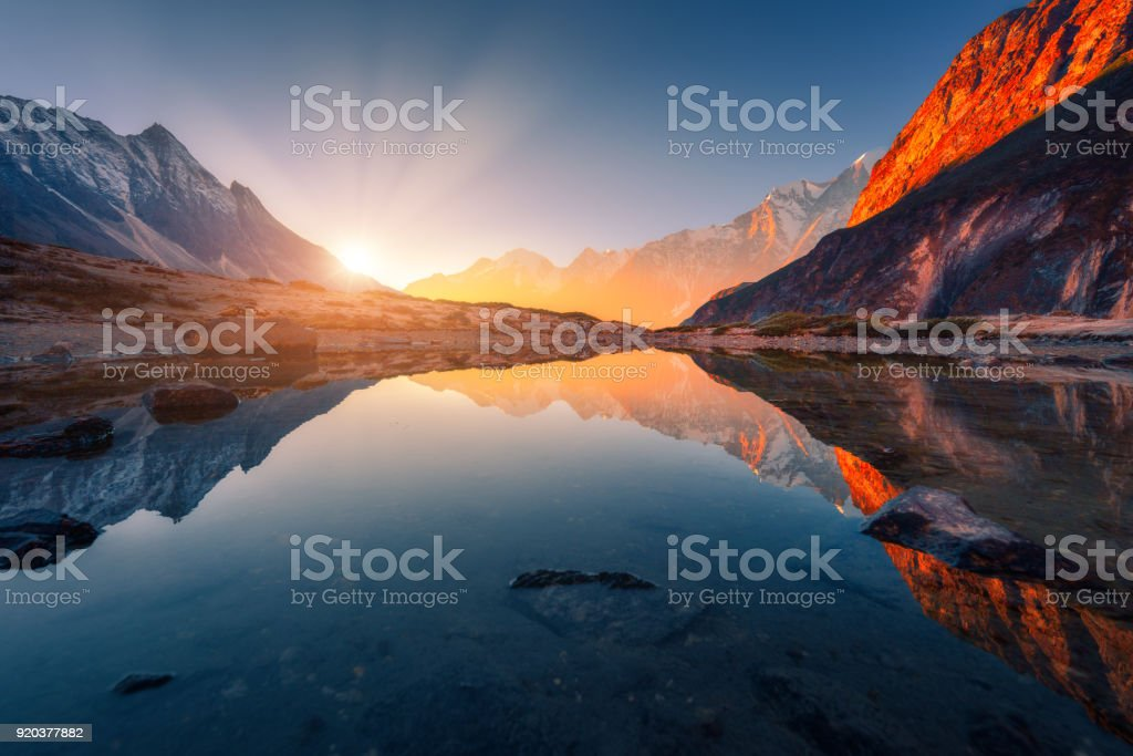 Beautiful landscape with high mountains with illuminated peaks, stones in mountain lake, reflection, blue sky and yellow sunlight in sunrise. Nepal. Amazing scene with Himalayan mountains. Himalayas stock photo