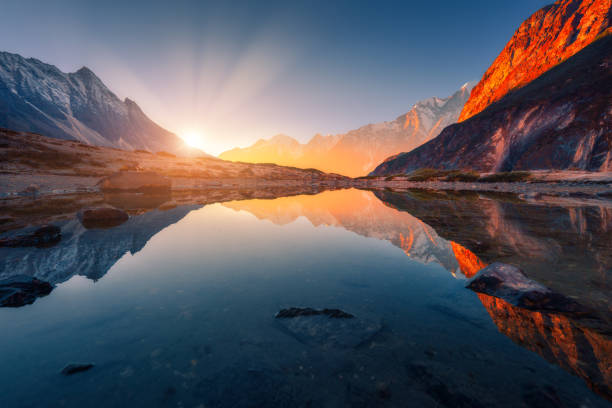 beautiful landscape with high mountains with illuminated peaks, stones in mountain lake, reflection, blue sky and yellow sunlight in sunrise. nepal. amazing scene with himalayan mountains. himalayas - composizione orizzontale foto e immagini stock
