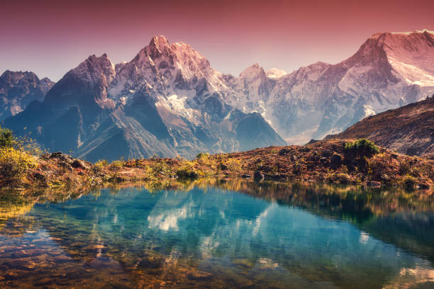 Beautiful landscape with high mountains with snow covered peaks, red sky reflected in lake. Mountain valley with reflection in water in sunset. Nepal. Amazing scene with Himalayan mountains. Nature stock photo