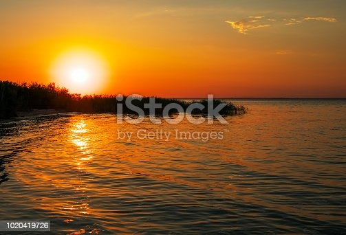 Beautiful landscape with sunset. Colorful sky. Shore of the reservoir, waves.