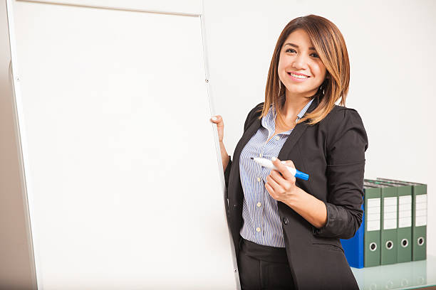 Beautiful language teacher during a class Portrait of a gorgeous Hispanic woman teaching Spanish and standing next to a flip chart flipchart stock pictures, royalty-free photos & images