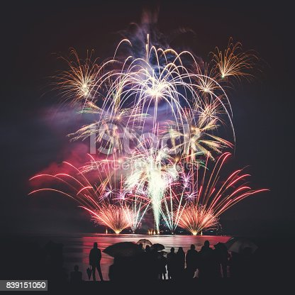 istock Beautiful large and colorful fireworks with unrecognizable crowd silhouettes people watching the show 839151050