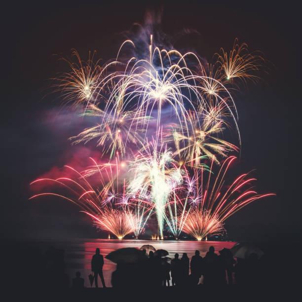 Magnifique feux d'artifice, grand et coloré, avec des gens de silhouettes méconnaissable foule regardant le spectacle - Photo