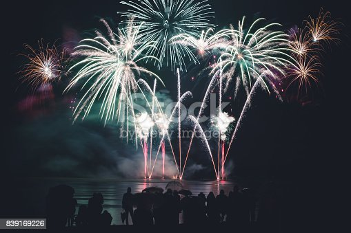 istock Beautiful large and colorful fireworks with unrecognizable crowd silhouettes people watching the show 839169226