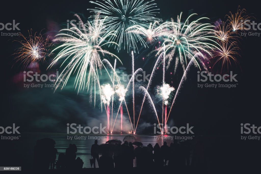 Beautiful large and colorful fireworks with unrecognizable crowd silhouettes people watching the show stock photo