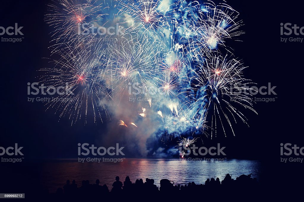 Beautiful large colorful fireworks display with unrecognizable crowd people watching stock photo