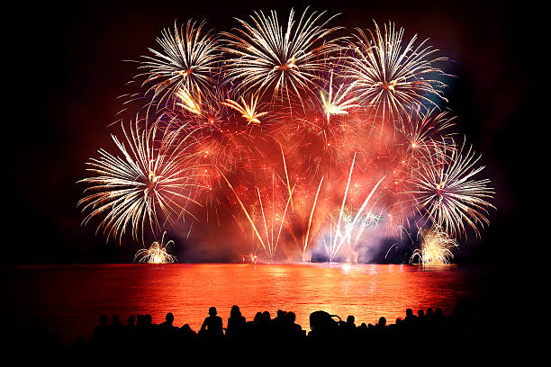 Beautiful large colorful fireworks display with unrecognizable crowd people watching - Photo