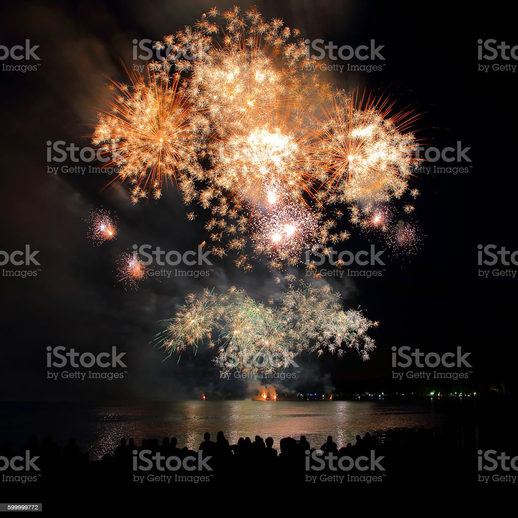 Beautiful large gold fireworks sparks with unrecognizable crowd people watching stock photo