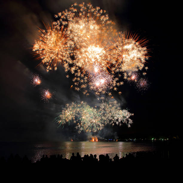 Beautiful large gold fireworks sparks with unrecognizable crowd people watching - Photo