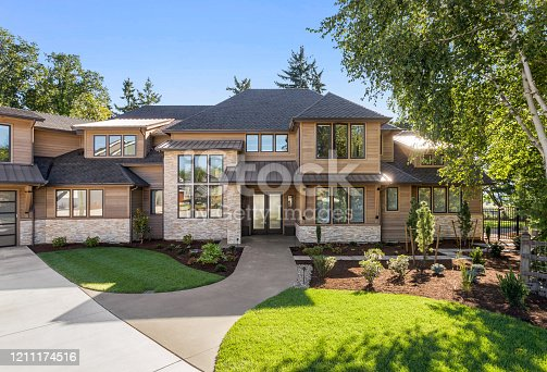 istock Beautiful large luxury home exterior on bright sunny day with green grass and blue sky 1211174516