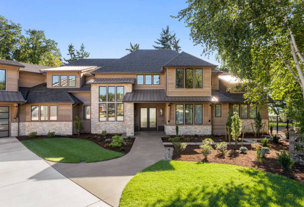 Beautiful large luxury home exterior on bright sunny day with green grass and blue sky Facade of home with manicured lawn, and backdrop of trees and blue sky home exterior stock pictures, royalty-free photos & images