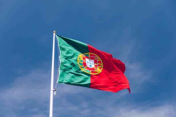Schöne große portugiesische Flagge weht im Wind gegen blauen Himmel. Portugiesische Flagge weht gegen blauen Himmel. Flagge von Portugal winkend, gegen blauen Himmel – Foto