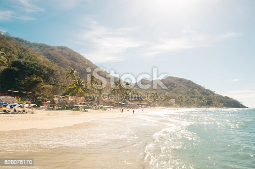 This is a horizontal color photograph of the Las Animas beach landscape near Puerto Vallarta, Mexico. Photographed on a sunny spring day. Incidental people are on the beach in the distance. Mountains rise above the shoreline.