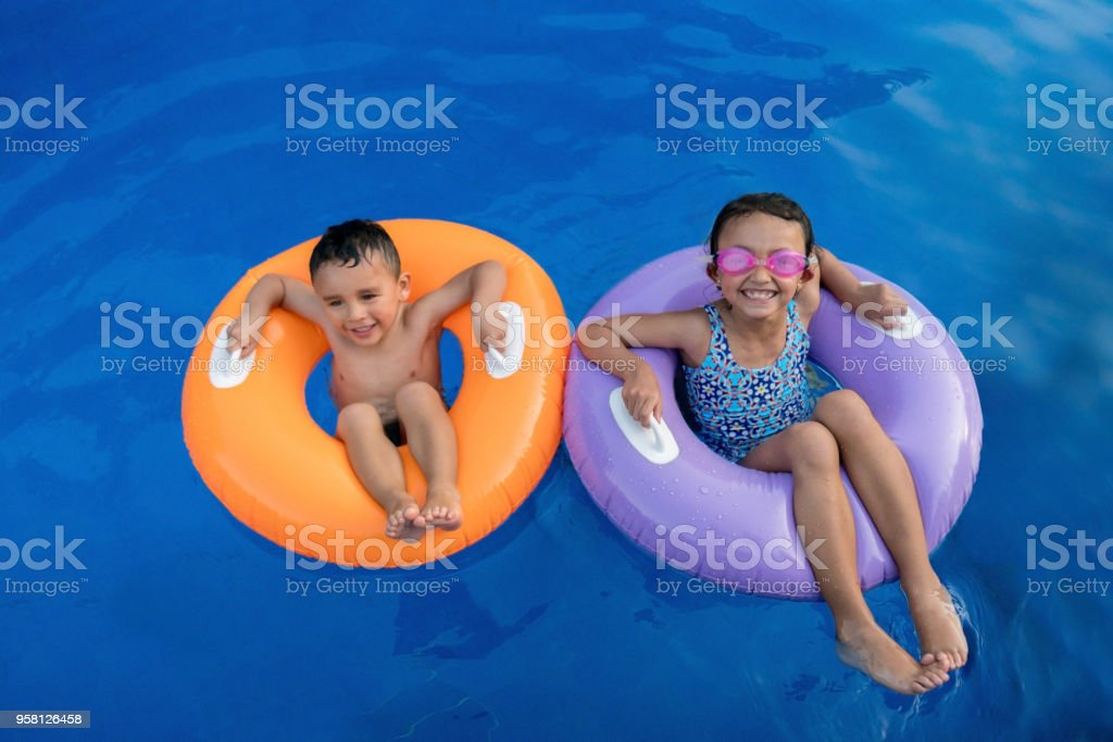 Beautiful Latin American Brother And Sister On Inflatable Tubes Looking At Camera With Excitement Royalty