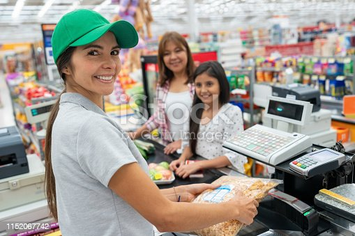 Beautiful latin american cashier registering products with bard code reader for customers while facing camera smiling very happy