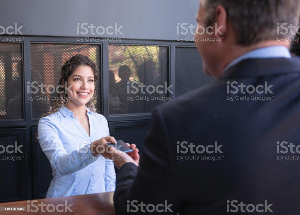 Beautiful latin american hotel receptionist handing hotel key to...