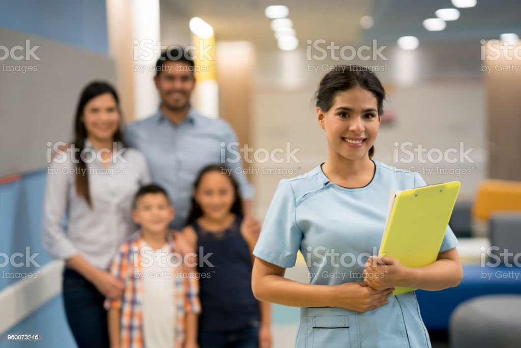 Beautiful latin american nurse holding a clipboard with a medical chart and family standing at the background all looking at camera smiling stock photo